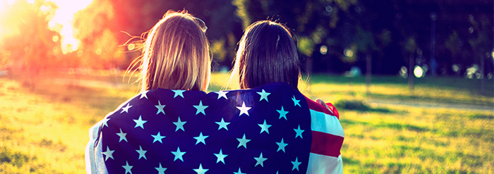 Young women with backs to camera holding U.S. flag over their shoulders and watching the sun set.