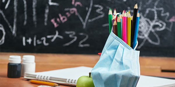 Photo of a teacher's desk with colored pencils, apple, notebook, pencil, and surgical mask with blackboard in background.