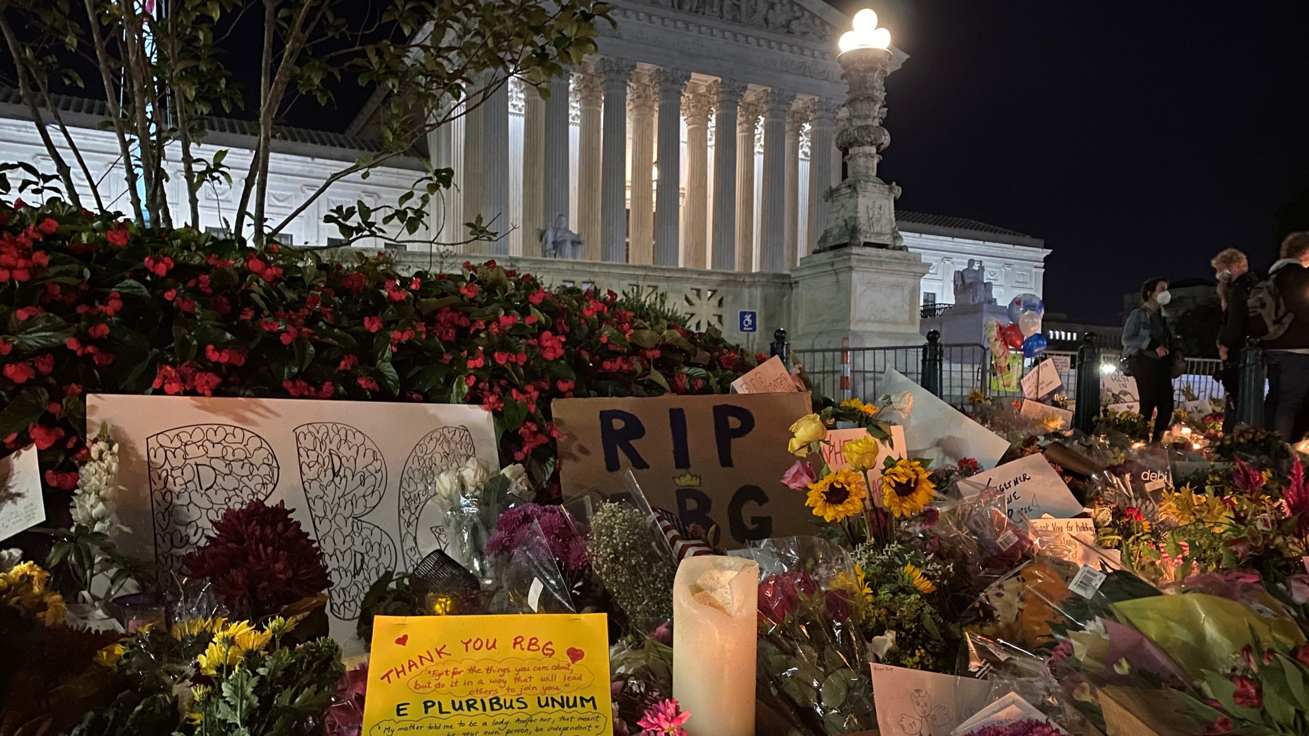 Photo of flowers and signs in front of the US Supreme Court.