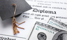 Image of graduation cap and stack of money on top of a diploma.